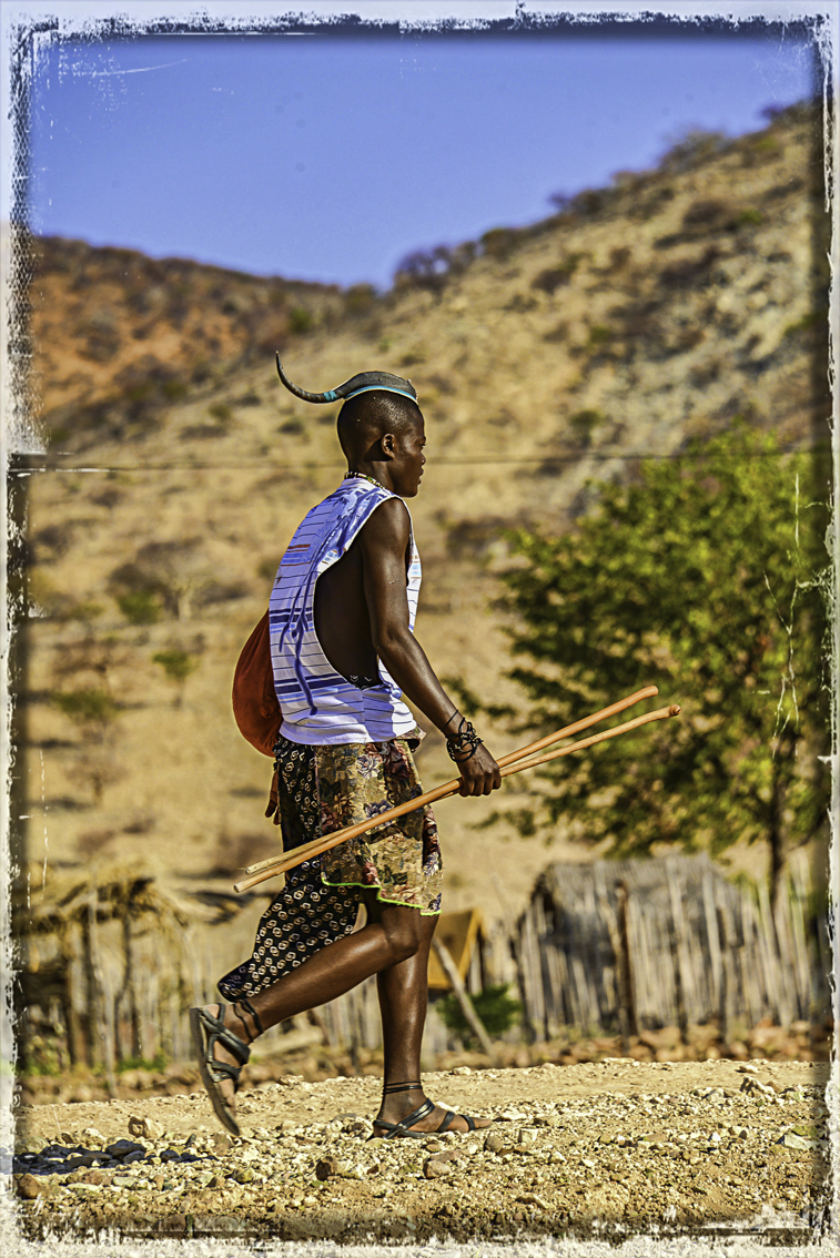 An unmarried Himba man, his hair 'whipped' backward